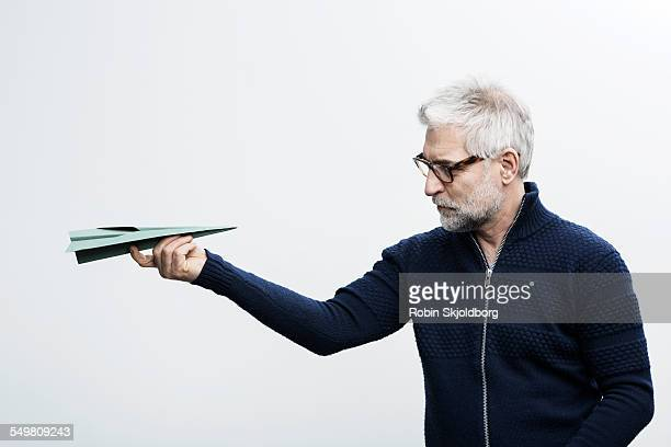 Grey haired holding paper airplane