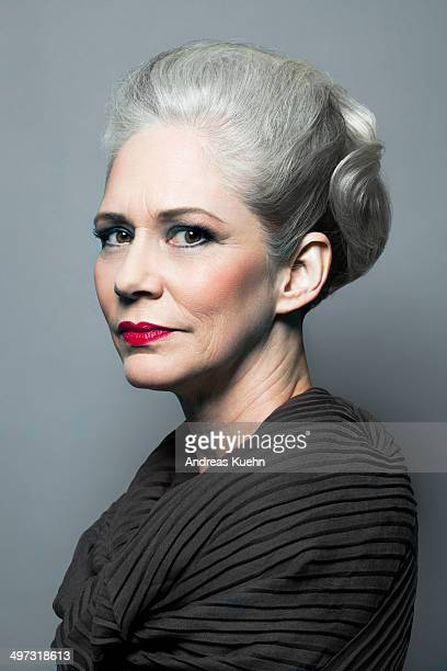 Grey haired lady with an updo and red lips.