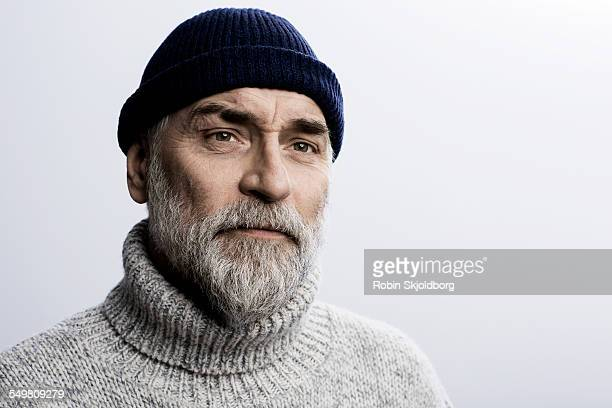 Grey haired man in sweater wearing hat
