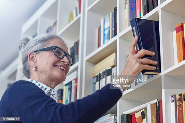 Grey haired mature woman selecting book from bookshelves