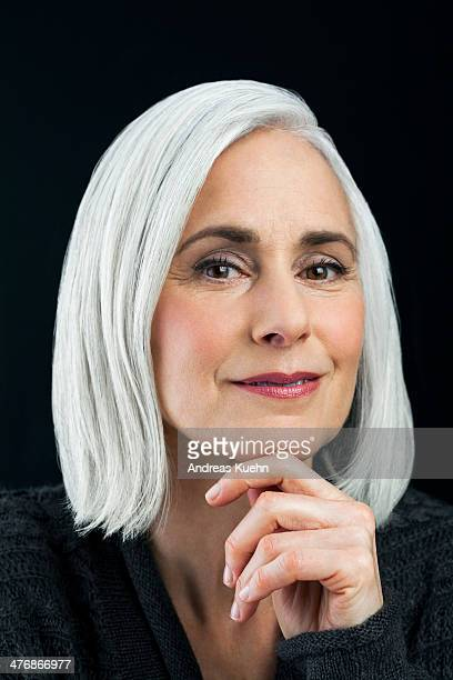 Grey haired mature woman with hand on chin.