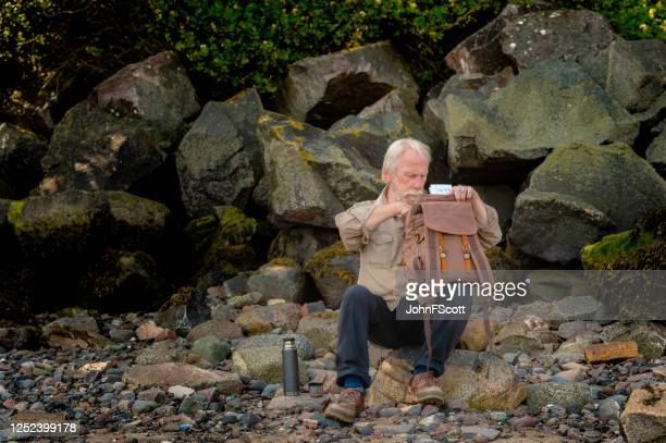grey haired senior man sitting on rocks at the shore looking inside his backpack - johnfscott stock pictures, royalty-free photos & images