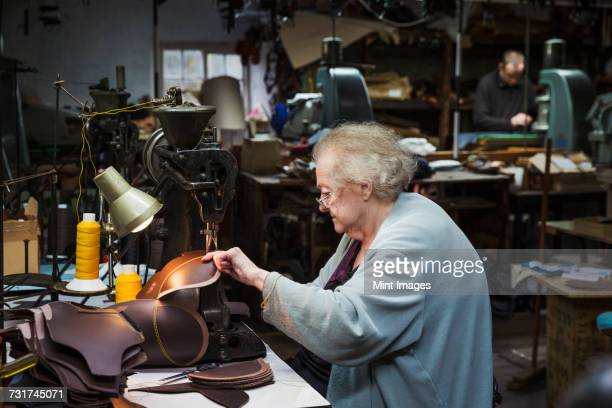 A grey haired senior worker, a woman sitting at a sewing machine in a shoemakers workshop.