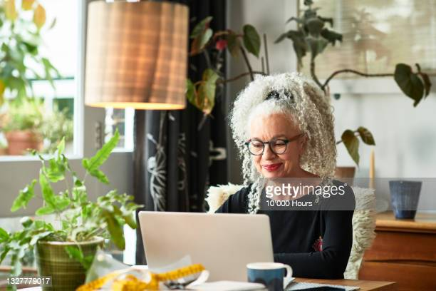 grey haired woman at home smiling in front of laptop - using laptop stock pictures, royalty-free photos & images