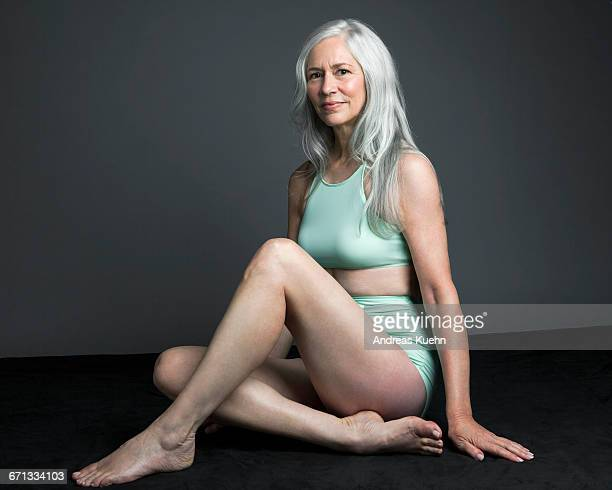Grey haired woman in swimsuit, sitting down.
