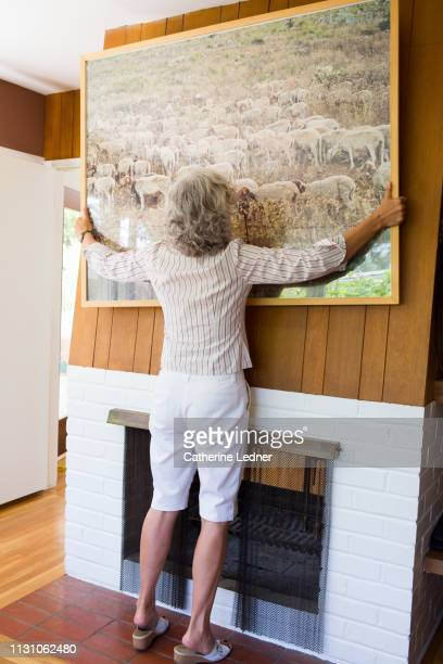 grey haired woman lifting large print off wall of 50's modern house