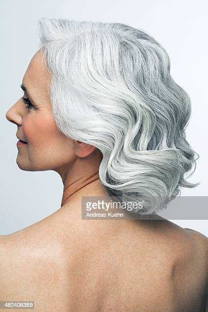 Grey haired woman looking to the side, back view.