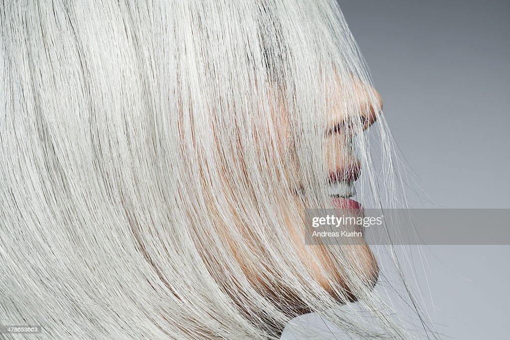 Grey haired woman profile with hair covering face. : Stock Photo