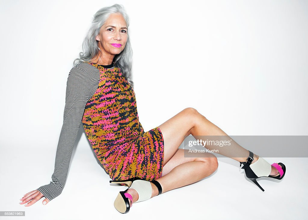 Woman with long, silvery, grey hair sitting on a white background wearing a funky outfit, pink lipstick and high heels.