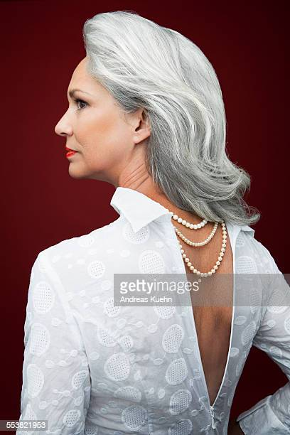 Grey haired woman with pearl necklaces, profile.