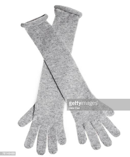 Grey knit gloves against white background