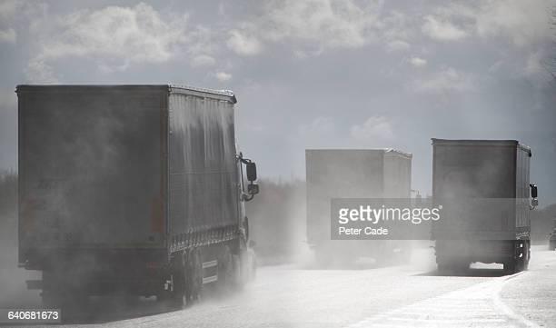 Grey lorries driving on wet road