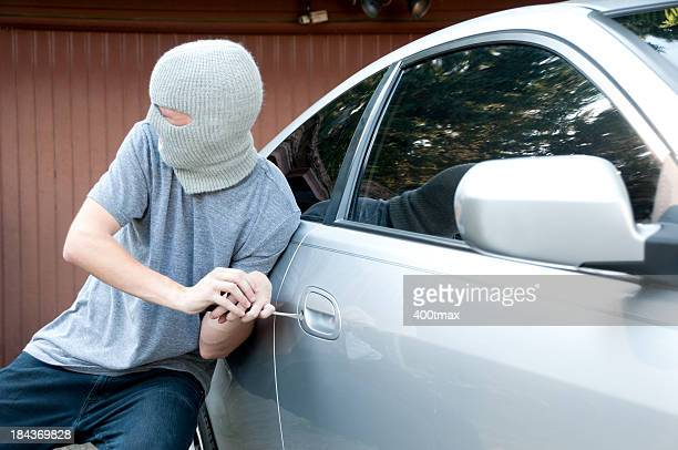 Grey masked teenager breaking into a car