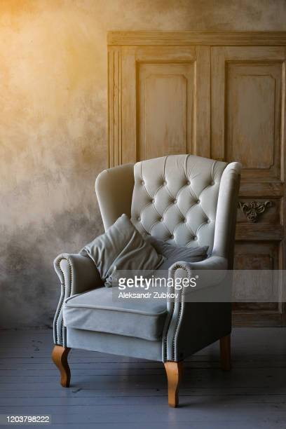 a grey or blue velour chair opposite the door to the living room. the interior of the room is designed in a retro style. tinted photo. - cosy stock pictures, royalty-free photos & images