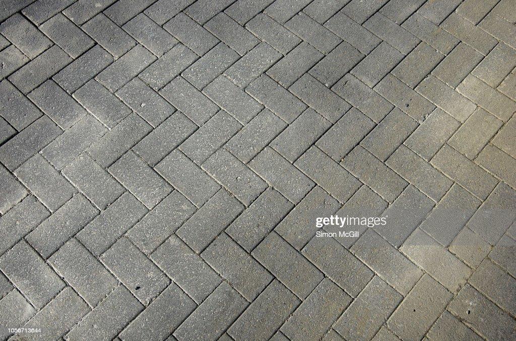 Grey rectangular paving stones in a herringbone pattern : Stock Photo