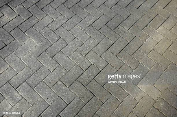 grey rectangular paving stones in a herringbone pattern - pavement stock pictures, royalty-free photos & images