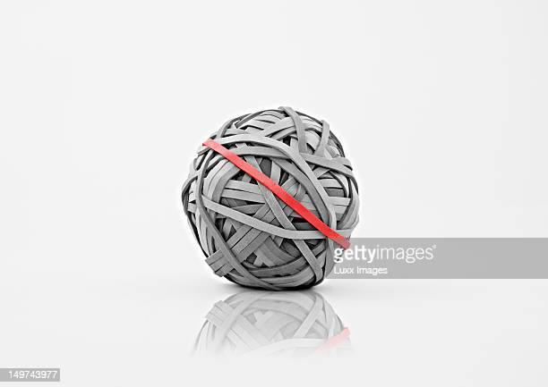 Grey rubber band ball with one red rubberband
