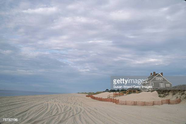 A grey shingle cottage sits on a dune overlooking a sandy beach in the Hamptons Long Island New York September 1984
