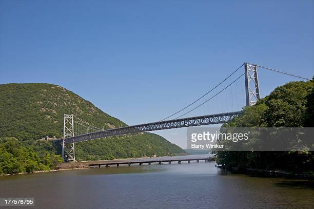 grey suspension bridge crossing water - bear mountain bridge stock pictures, royalty-free photos & images