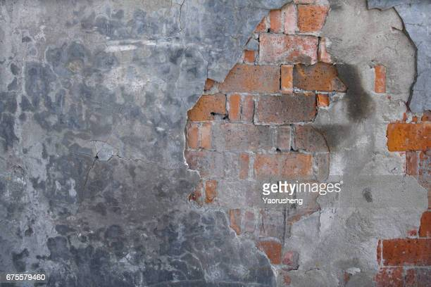 grey wall with broken bricks and chipped being watched