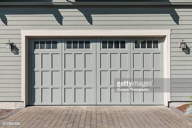 Grey-green garage door at mid-morning.