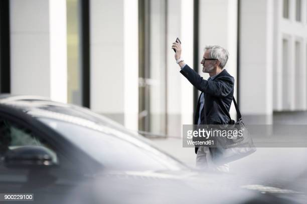 grey-haired businessman calling a taxi in the city - waving gesture stock photos and pictures