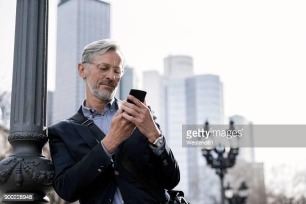 grey-haired businessman looking at smartphone standing next to street lamp - hesse duitsland stockfoto's en -beelden