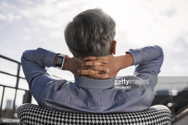 Grey-haired businessman relaxing in chair on balcony