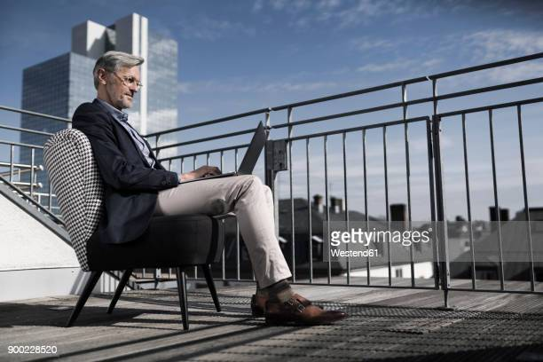 Grey-haired businessman sitting on balcony using laptop