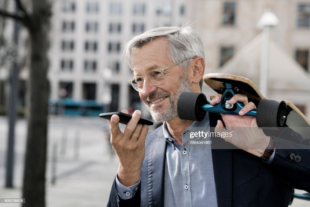 Grey-haired businessman with longboard and smartphone : Stock Photo