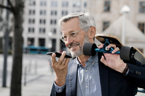 Grey-haired businessman with longboard and smartphone - gettyimageskorea