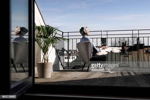 grey-haired man relaxing in chair on balcony - geländer stock-fotos und bilder