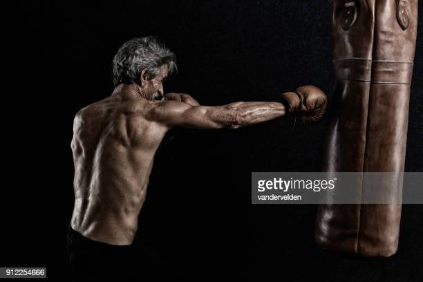 Grey-haired retired boxer sweating during his workout