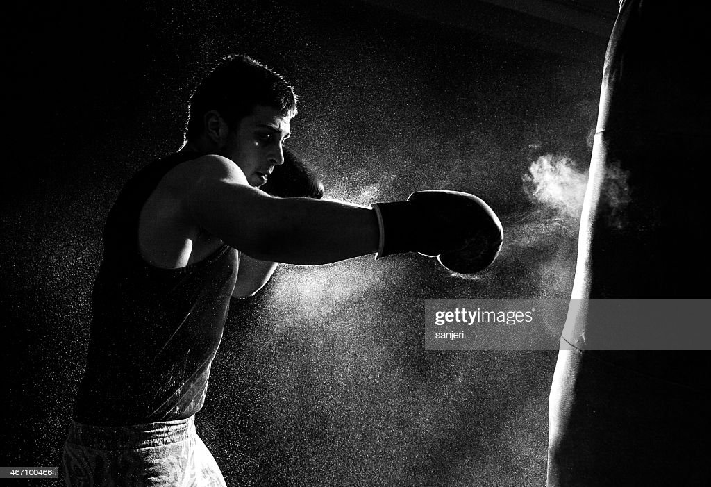 Greyscale Image Of A Boxer Having Go At The Punching Bag