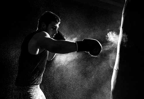 Greyscale image of a boxer having a go at the punching bag 467100466