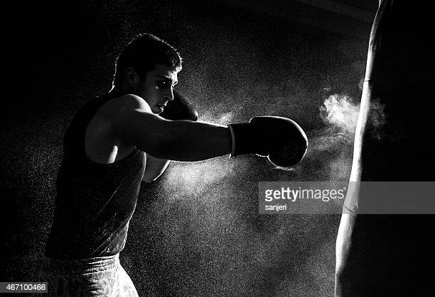 Greyscale image of a boxer having a go at the punching bag