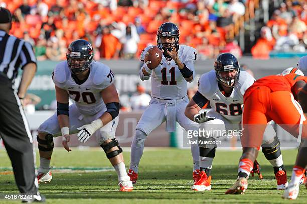 Greyson Lambert takes the snap from Luke Bowanko of the Virginia Cavaliers during fourth quarter action against the Miami Hurricanes on November 23...