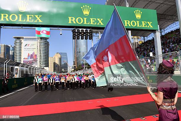 A grid girl holds the Azeri national flag before the start of the European Formula One Grand Prix at the Baku City Circuit on June 19 2016 in Baku /...