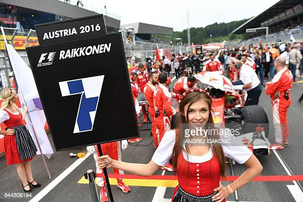 A grid girl holds the number 7 of Ferrari's Finnish driver Kimi Raikkonen before start the Formula One Grand Prix of Austria at the Red Bull Ring in...