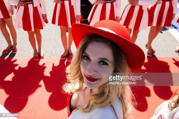 TOPSHOT A grid girl poses for a photographer ahead of the Formula One Russian Grand Prix at the Sochi Autodrom circuit in Sochi on April 30 2017 /...