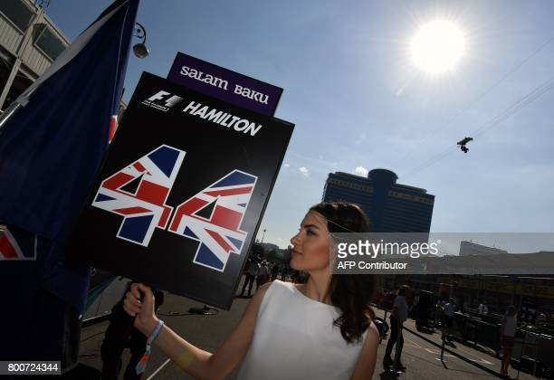 A grid girl poses with the number 44 of Mercedes' British driver Lewis Hamilton prior to the start of the Formula One Azerbaijan Grand Prix at the...
