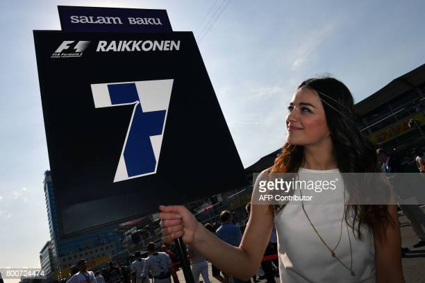 A grid girl poses with the number 7 of Ferrari's Finnish driver Kimi Raikkonen prior to the start of the Formula One Azerbaijan Grand Prix at the...