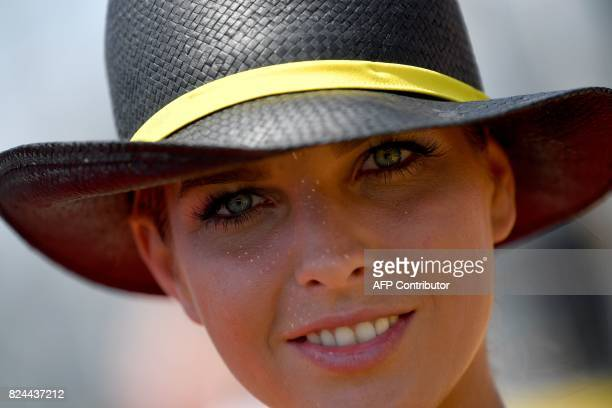 A grid girl smiles at the Hungaroring racing circuit in Budapest on July 30 prior to the Formula One Hungarian Grand Prix / AFP PHOTO / ANDREJ...