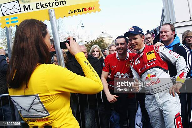 A grid girl takes a photo of Swedish Audi driver Mattias Ekstroem during the DTM touring car presentation on April 22 2012 in Wiesbaden Germany