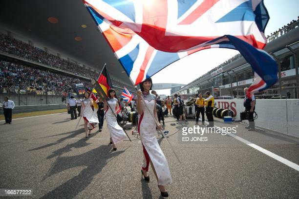 A grid girl walks off the starting grid prior to the start of the Formula One Chinese Grand Prix in Shanghai on April 14 2013 AFP PHOTO / Ed Jones