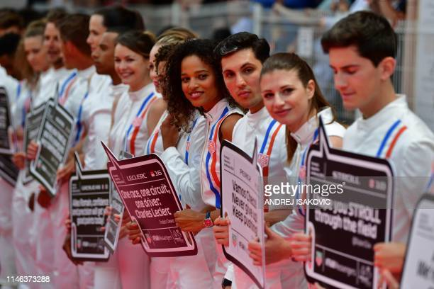 Grid girls and boys hold placards with messages for Formula One drivers ahead of the Monaco Formula 1 Grand Prix at the Monaco street circuit on May...