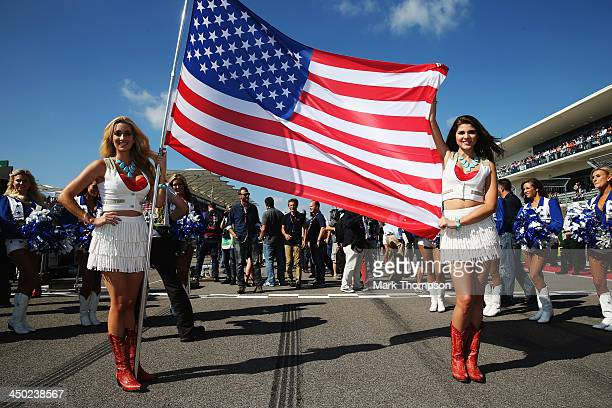 Grid girls carry the national flag of the United States on the grid before the start of the United States Formula One Grand Prix at Circuit of The...