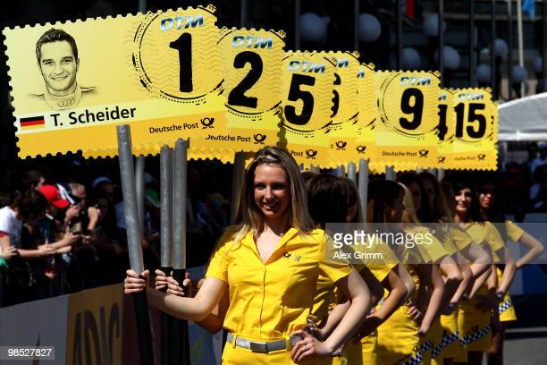 Grid girls hold up signs with the names of this year's drivers during the presentation of the German Touring Car Championship DTM in front of the...