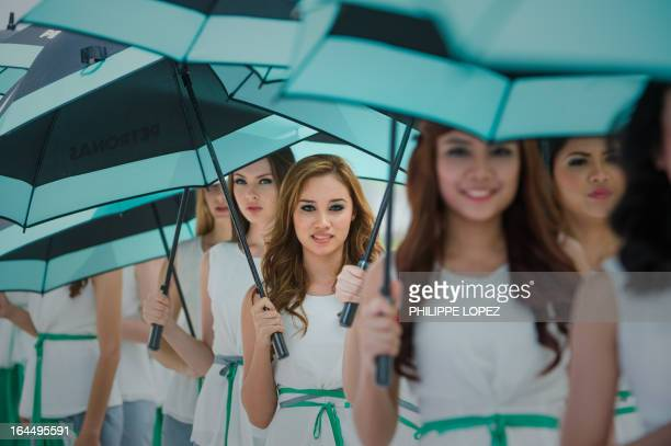 Grid girls line up before the start of the Formula One Malaysian Grand Prix in Sepang on March 24 2013 AFP PHOTO / Philippe Lopez