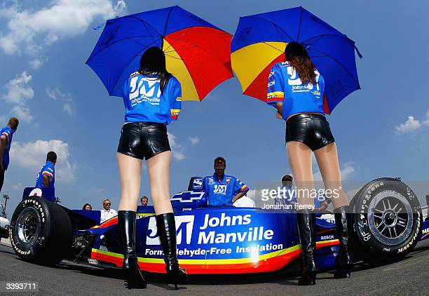 Grid girls shade Mark Taylor with their umbrellas as he sits in his Panther Chevrolet Dallara during qualifying for the IRL IndyCar Series...